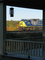 CSX 8756 seen through the front porch of a old house on Pulaski
